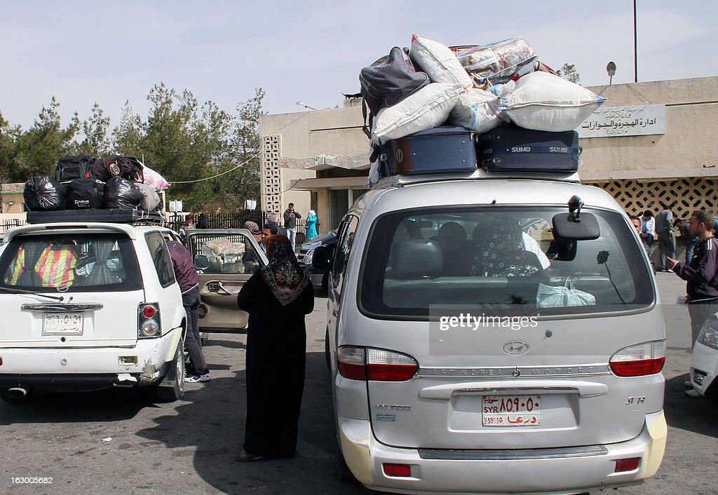 Syrian people stand near vehicles on March 3, 2013 in the Syrian city of al-Jdeideh after crossing the Lebanese-Syrian border in al-Masnaa on their way back to Syria.