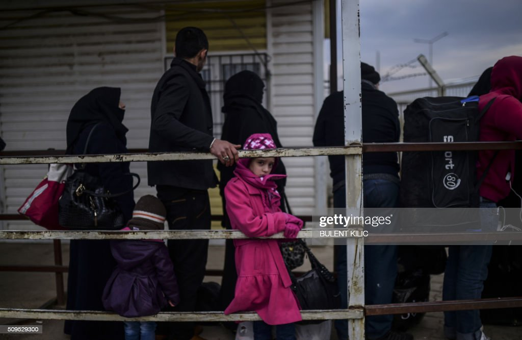 Syrian people wait in front of the Oncupinar crossing gate to go back to Syria, near the town of Kilis, in south-central Turkey, on February 11, 2016. Turkish President Recep Tayyip Erdogan on February 11 threatened to send the millions of refugees in Turkey to European Union (EU) member states, as NATO agreed to deploy ships to the Aegean Sea to ease the migrant crisis. / AFP / BULENT KILIC