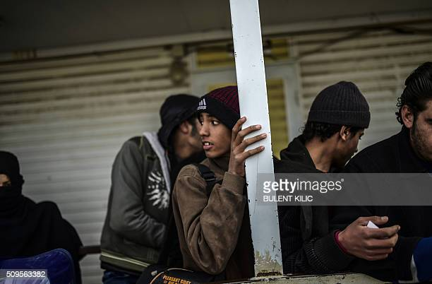 Syrian people wait in front of the Oncupinar crossing gate to go back to Syria near the town of Kilis in southcentral Turkey on February 11 2016...
