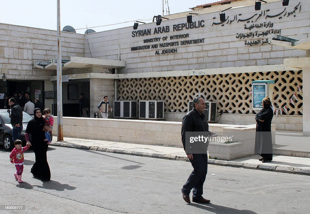 Syrian people walk past immigration buildings on March 3, 2013 in the Syrian city of al-Jdeideh after crossing the Lebanese-Syrian border in al-Masnaa on their way back to Syria.