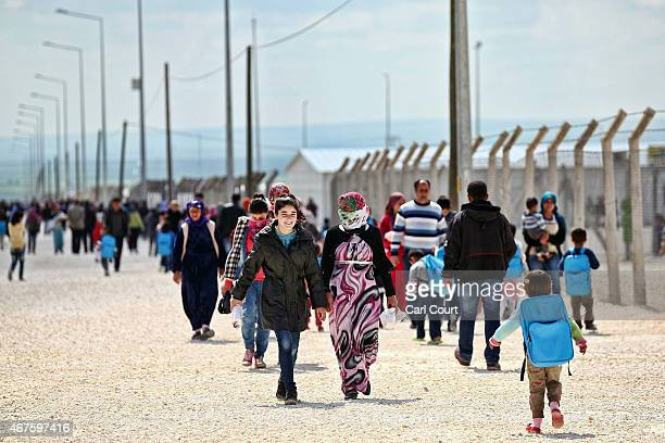 Syrian people walk through Suruc refugee camp on March 25 2015 in Suruc Turkey The camp is the largest of its kind in Turkey with a population of...