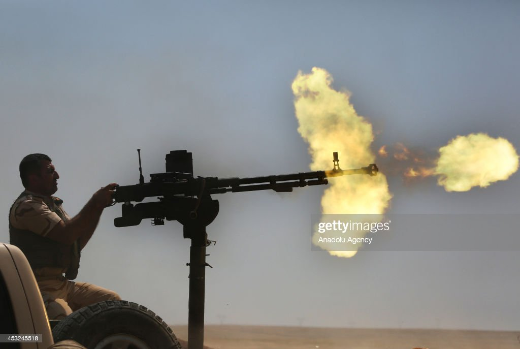 Syrian People's Protection Units (YPG) members fight against Islamic State of Iraq and the Levant (ISIL) in Rabia town, Mosul, Iraq on August 6, 2014. YPG members and Kurdish Peshmerga forces fire to howitzers and machine guns against ISIL during the clashes.