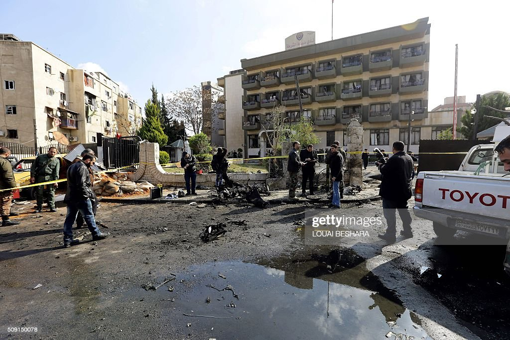 Syrian policemen and security forces gather at the site of a suicide attack at a police officer's club in the Masaken Barzeh district of the capital Damascus on February 9, 2016. The Syrian Observatory for Human Rights said about 20 people had also been wounded, adding that policemen were among the dead and injured. BESHARA
