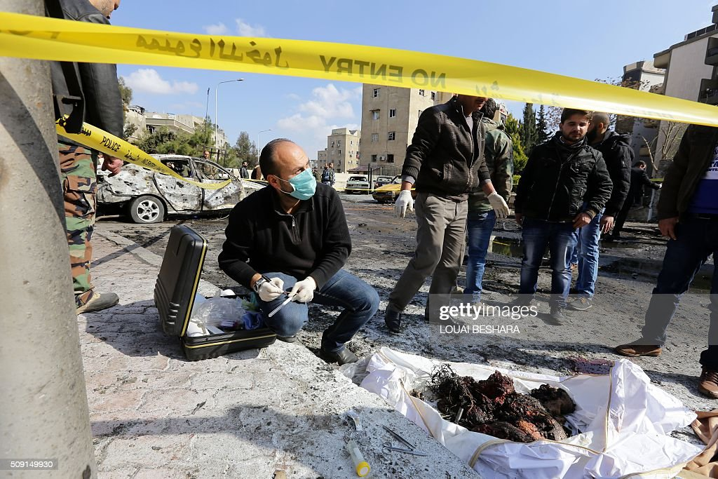 Syrian policemen inspect the site of a suicide attack at a police officer's club in the Masaken Barzeh district of the capital Damascus on February 9, 2016. The Syrian Observatory for Human Rights said about 20 people had also been wounded, adding that policemen were among the dead and injured. BESHARA