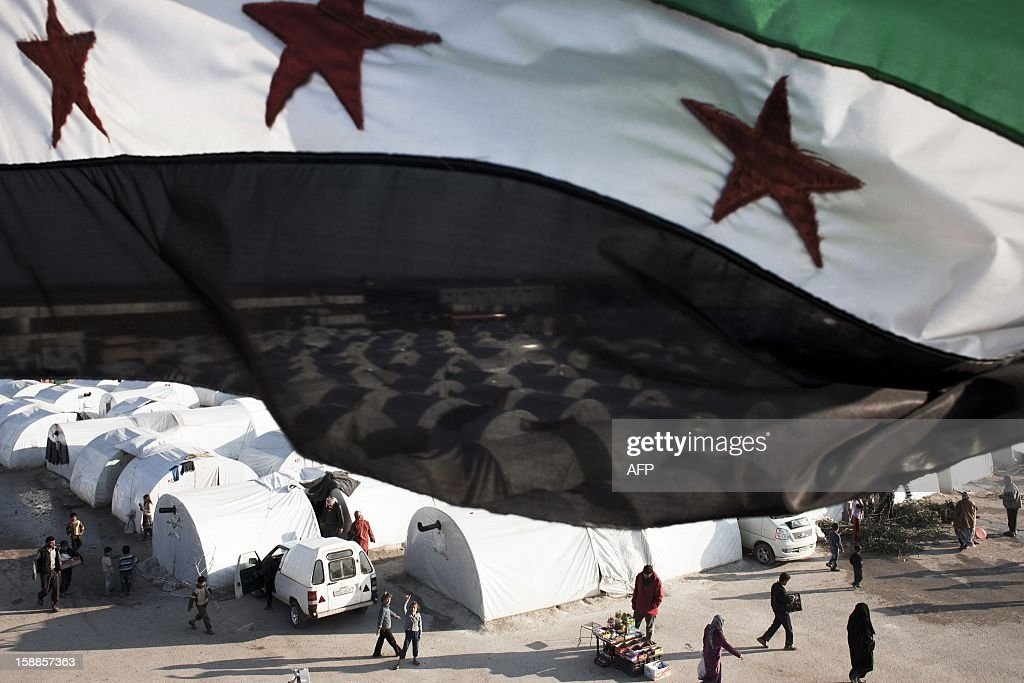 A Syrian pre-Baath flag flies over the Bab al-Salama refugee camp on the Syrian-Turkish border on January 1, 2013. Turkey, which supports the insurgency, is housing a total of some 150,000 Syrian refugees at camps near the border.