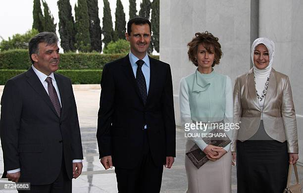 Syrian President Bashar alAssad and his wife Asma greet Turkish President Abdullah Gul and his wife Hayrunnisa upon their arrival at alShaab Palace...