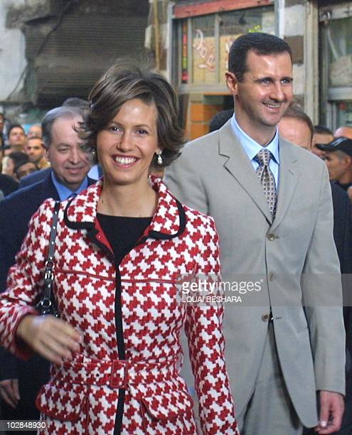 Syrian President Bashar alAssad and his wife Asma smile as they walk in old Damascus 20 October 2003 joined by the Spanish royals who ar on a...