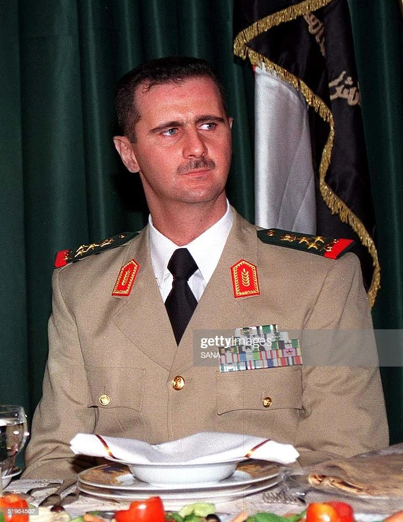 Syrian President Bashar al-Assad (R) attends a dinner in Damascus late 01 August 2000, during a ceremony marking the Army Day.