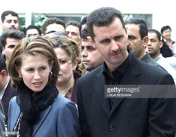 Syrian President Bashar alAssad looks over along with his wife Asma as they walk through the Sham Fair in Damascus 26 April 2002 The annual...