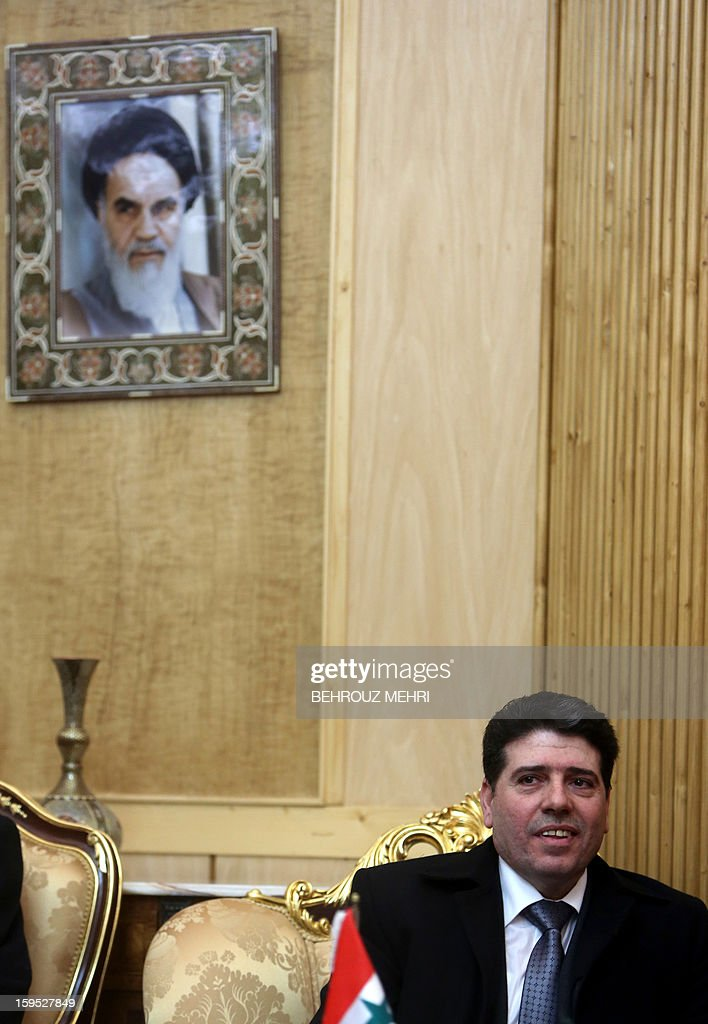 Syrian Prime Minister Wael al-Halaqi sits under a portrait of Iran's founder of Islamic Republic, Ayatollah Ruhollah Khomeini upon his arrival at Tehran's Mehrabad airport on January 15, 2013, a week after Syrian rebels freed 48 Iranians held hostage for more than five months.