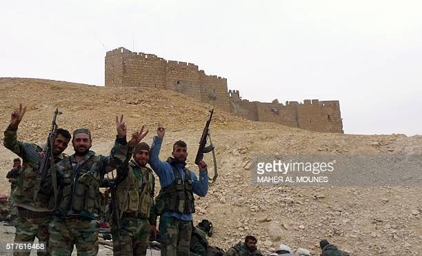Syrian progovernement forces gesture next to the Palmyra citadel on March 26 during a military operation to retake the ancient city from the jihadist...