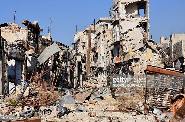 Syrian progovernment fighter walks amidst the rubble in old Aleppo's Jdeideh neighbourhood on December 9 2016 Syria's government has retaken at least...