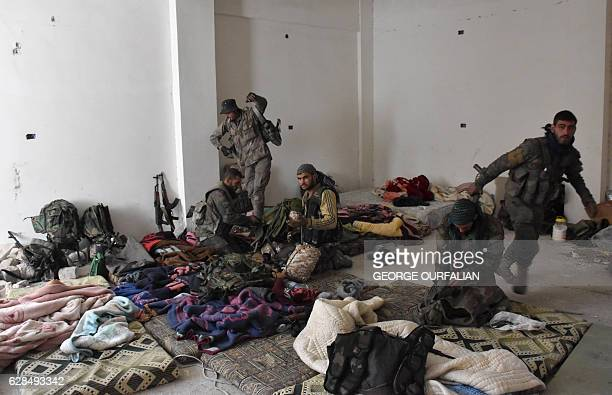 Syrian progovernment forces check their equipment as they hold a position in the newly retaken area of Sahat alMelh and Qasr alAdly in Aleppo's Old...