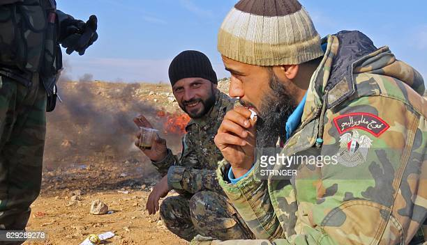 Syrian progovernment forces drink coffee as they rest in Aleppo's Sheikh Saeed district on December 12 after troops retook the area from rebel...