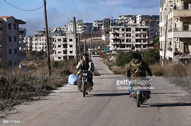 Syrian progovernment forces drive motorbikes in the strategic town of Salma in the coastal Latakia province on January 15 following its recapture...