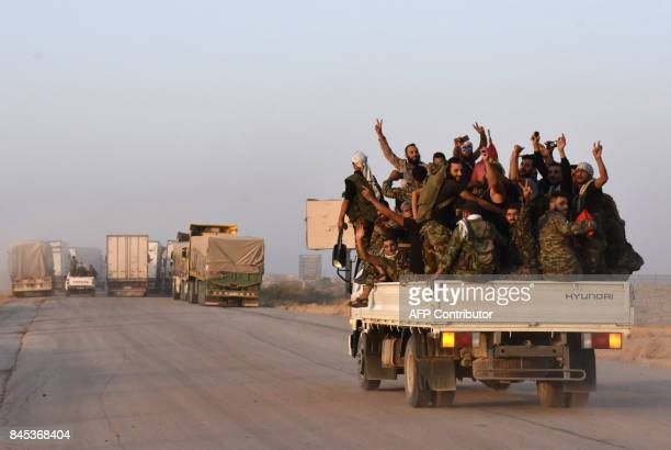 Syrian progovernment forces flash the sign for victory in the back of vehicle on the outskirts of the eastern city of Deir Ezzor on September 10 as...