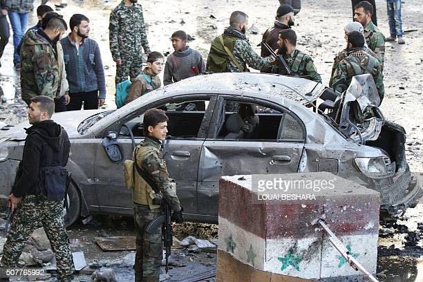 Syrian progovernment forces gather at the site of suicide bombings in the area of a revered Shiite shrine in the town of Sayyida Zeinab on the...