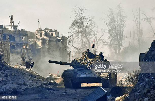TOPSHOT Syrian progovernment forces manoeuver a tank in the newly retaken area of Sahat alMelh and Qasr alAdly in Aleppo's Old City on December 8...