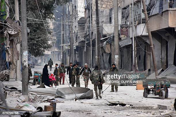 TOPSHOT Syrian progovernment forces patrol Aleppo's eastern alSalihin neighbourhood on December 12 2016 after troops retook the area from rebel...