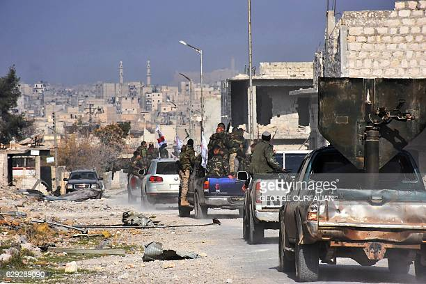 TOPSHOT Syrian progovernment forces patrol Aleppo's Sheikh Saeed district on December 12 after troops retook the area from rebel fighters / AFP /...