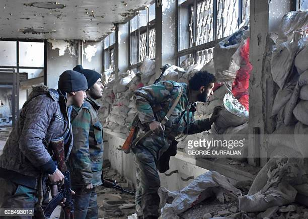 Syrian progovernment forces patrol an abandoned building in the newly retaken area of Sahat alMelh and Qasr alAdly in Aleppo's Old City on December 8...