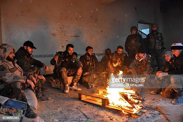 TOPSHOT Syrian progovernment forces rest by a fire as they advance in the Jisr alHaj neighbourhood during the ongoing military operation to retake...