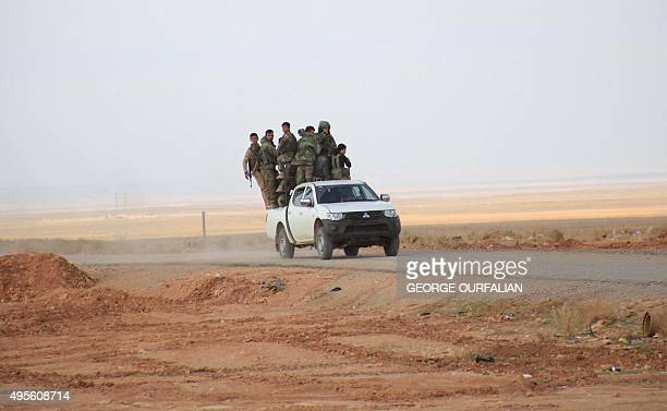 Syrian progovernment forces ride on a pickup truck on the only road into the governmentheld side of Aleppo after they reported recaptured it from...