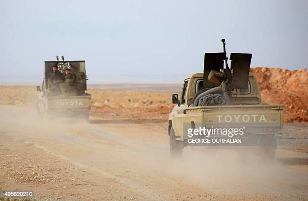 Syrian progovernment forces ride on pickup trucks equipped with weapons on the only road into the governmentheld side of Aleppo after they reported...