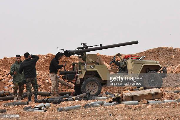 Syrian progovernment forces stand next to a 106mm recoilless antitank cannon as residents fleeing the eastern part of Aleppo arrive at the Jabal...