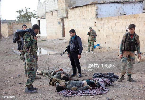 Syrian progovernment forces stand next to the bodies of alleged jihadists near the town of Safireh southeast of Syria's second city Aleppo on October...