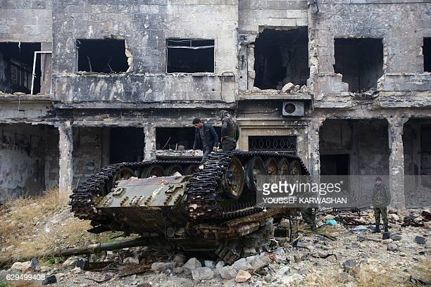 Syrian progovernment forces stand on a tank near the ancient Umayyad mosque in the old city of Aleppo on December 13 after they captured the area...