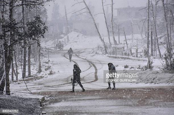 TOPSHOT Syrian progovernment forces walk as snow falls in Aleppo on December 21 2016 The last residents hoping to leave rebelheld Aleppo waited in...