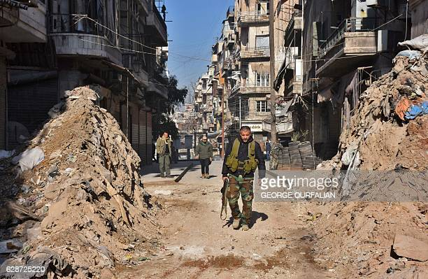 TOPSHOT Syrian progovernment forces walk through a barricade in old Aleppo's Jdeideh neighbourhood on December 9 2016 Syria's government has retaken...