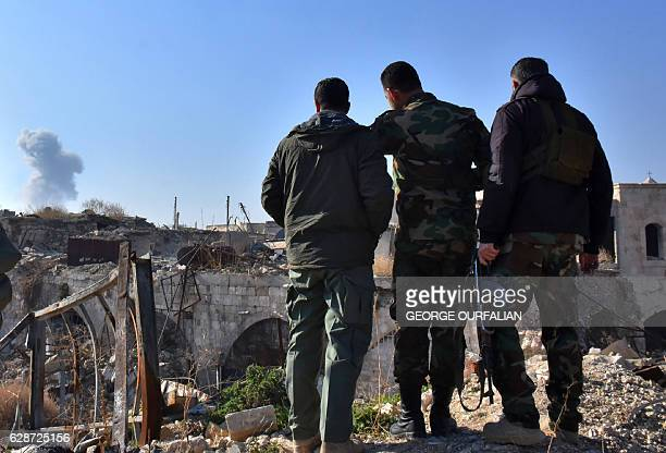 TOPSHOT Syrian progovernment forces watch as smoke billows in the background in old Aleppo's Jdeideh neighbourhood on December 9 2016 Syria's...