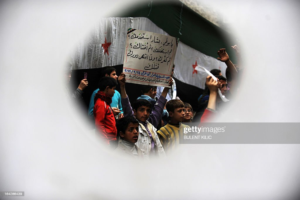 Syrian protesters are seen through a hole in a flag as they hold a sign blaming Syrian President Bashar al-Assad for a deadly mosque bombing that killed Sheikh Mohammed Saeed al-Bouti during an anti-regime demonstration in the northern city of Aleppo on March 22, 2013. EU foreign ministers mulled a contested push by Britain and France to lift or amend a Syria arms embargo to help tip the balance in the country's more than two-year conflict.