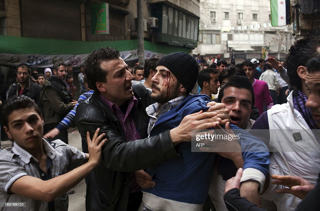 Syrian protestors help a man who was injured after an argument with a fellow demonstrator during a rally to mark second anniversary of the Syrian conflict, in Bustan al-Qasr district of Aleppo on March 15, 2013. Syria's protesters took to the streets across flashpoint areas, chanting slogans against President Bashar al-Assad and vowing not to be oppressed again as the anti-regime revolt entered its third year.