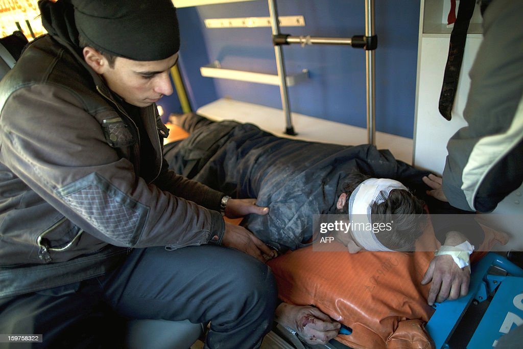 Syrian rebel checks on a wounded comrade lying inside an ambulance in the war-torn northern city of Aleppo on January 12, 2013. The accident and emergency centre in Aleppo uses an abandoned supermarket to conceal a fleet of 16 ambulances, just 10 of which are in working order and are driven by 22 staff members.