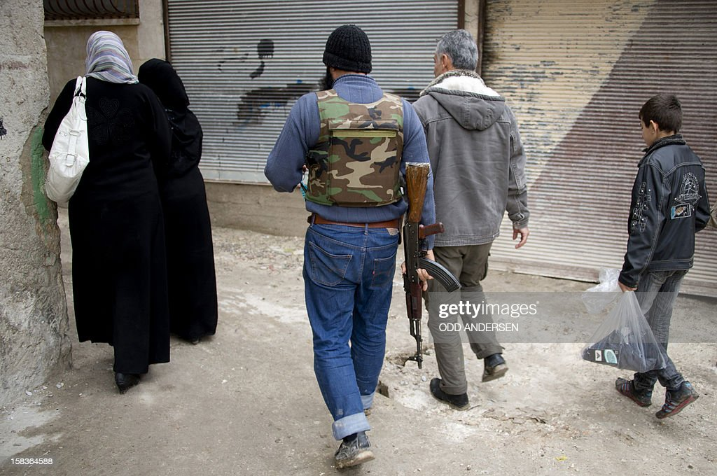 A Syrian rebel fighter and civilians walk along an alleyway in the northern town of Darkush on December 14, 2012. The United States said it plans to deploy two Patriot missile batteries to Turkey along with 400 troops to help defend its ally against potential threats from neighbouring Syria. AFP PHOTO / ODD ANDERSEN