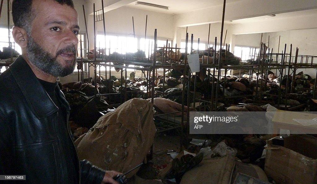 Syrian rebel fighter chief inspects a dormitory in the Syrian army Base 46 after its capture, near the northern city of Aleppo, on November 21, 2012. Defected General Mohammed Ahmed al-Faj, who commanded the assault, hailed the capture of the Base 46 as 'one of our biggest victories since the start of the revolution' against President Bashar al-Assad. AFP PHOTO/HERVE BAR