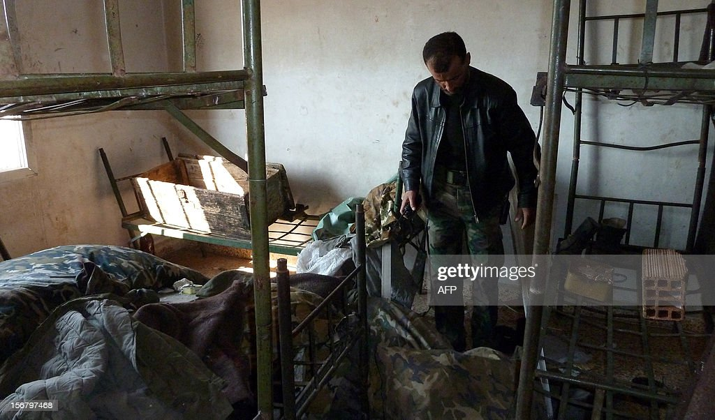 Syrian rebel fighter chief inspects the damage to a dormitory in the Syrian army Base 46 after its capture, near the northern city of Aleppo, on November 21, 2012. Defected General Mohammed Ahmed al-Faj, who commanded the assault, hailed the capture of the Base 46 as 'one of our biggest victories since the start of the revolution' against President Bashar al-Assad. AFP PHOTO/HERVE BAR