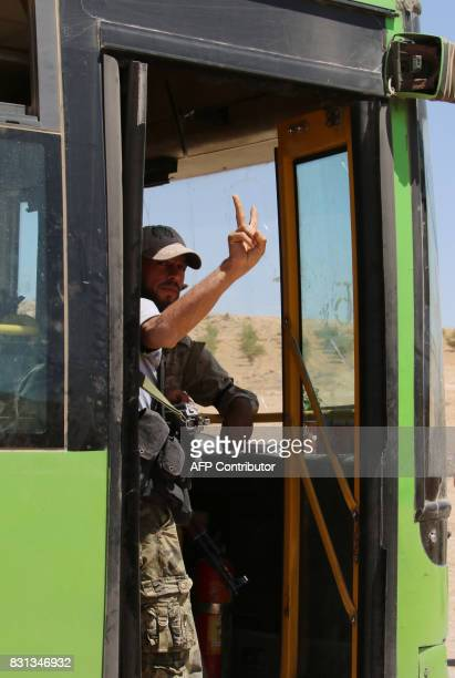 A Syrian rebel fighter gestures as he is being evacuated from northeastern Lebanon on August 14 2017 in a mountainous area around the Lebanese town...