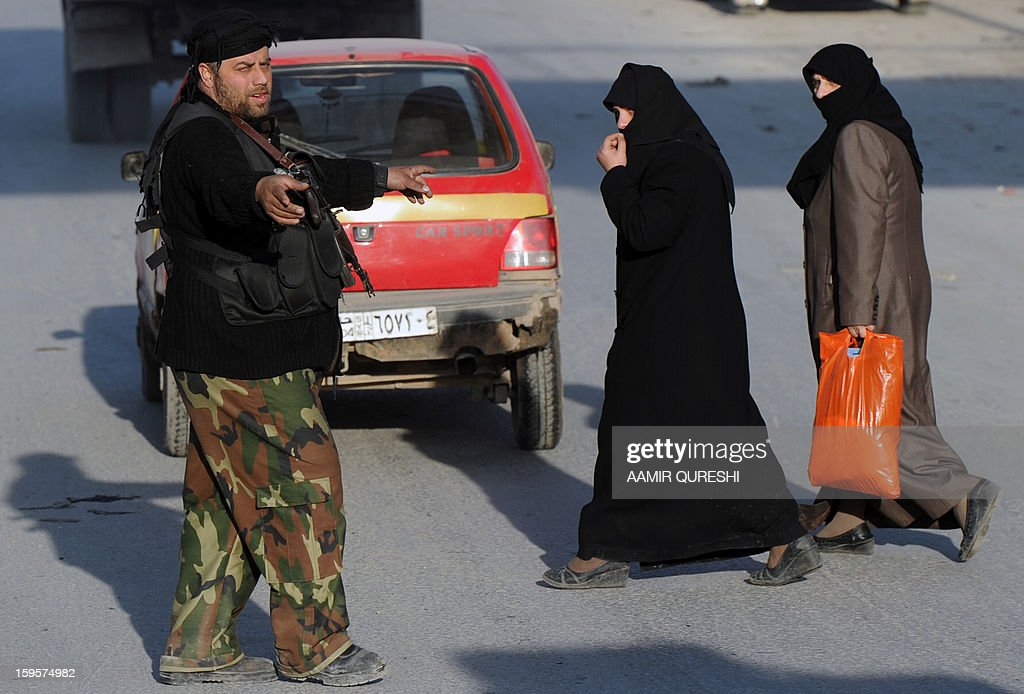 A Syrian rebel fighter helps women cross the road at a check point in Aleppo's old city on January 16, 2013. Syria's transport sector has lost 3.6 billion Syrian pounds ($391 million/294 million euros) since the uprising against President Bashar al-Assad broke out in March 2011, state media reported.