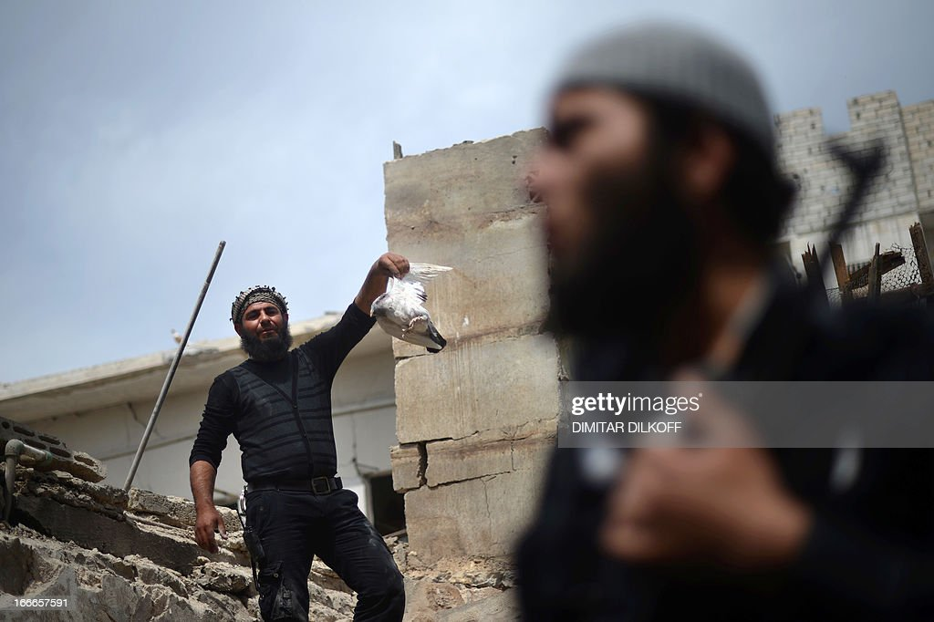 A Syrian rebel fighter holds a wounded pigeon in the remains of a destroyed house following an airstrike by the Syrian airforce in the northern Syrian city of Aleppo on April 15, 2013. The conflict in Syria, which is now in its third year, has cost 70,000 lives, according to the United Nations.