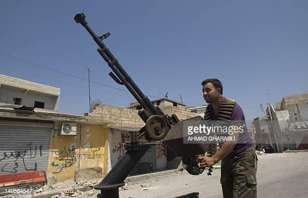 A Syrian rebel fighter loads an antiaircraft machinegun in the northern town of Atareb 25 kms east of Syria's second largest city Aleppo on July 31...
