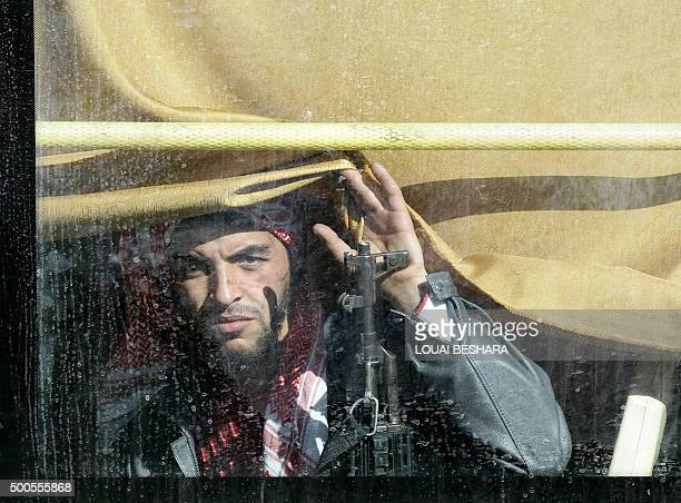 A Syrian rebel fighter looks on from a bus as hundreds of civilians and rebel forces began evacuating the last oppositionheld district of Waer in the...