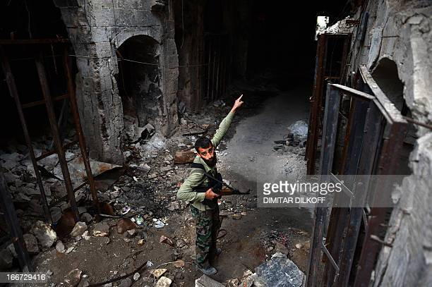 A Syrian rebel fighter points to destruction in the Umayyad Mosque complex in the old part of Syria's northern city of Aleppo on April 16 2013 After...