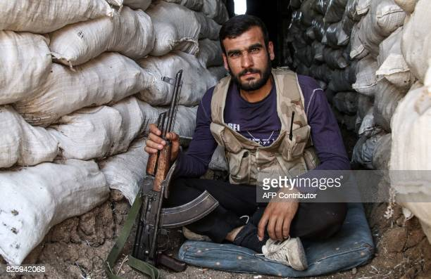 A Syrian rebel fighter poses for a picture with a Kalashnikov assault rifle while sitting in a fortified position in the central Syrian rebelheld...