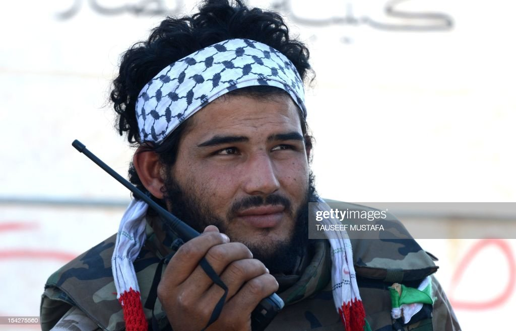 A Syrian rebel fighter speaks on a walkie talkie as he and others head towards the front line in al-Bab, 30 kilometers from the northeastern Syrian city of Aleppo, on October 17, 2012. Rebels downed a helicopter in fierce fighting with troops seeking to retake a key Syrian town, a watchdog said, as peace envoy Lakhdar Brahimi warned the conflict risks setting the region ablaze. AFP PHOTO/TAUSEEF MUSTAFA