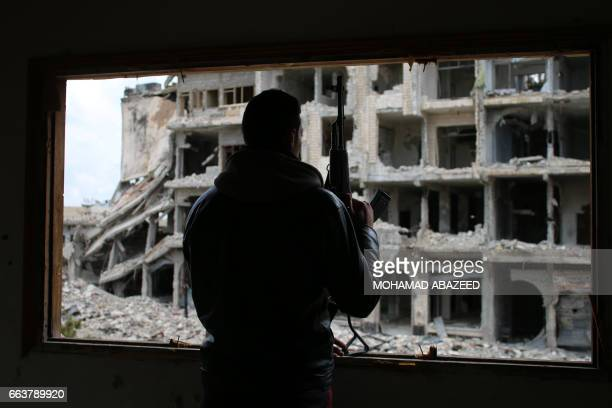 Syrian rebel fighter stands behind a window in a heavily damaged neighbourhood of Daraa in southern Syria on April 2 2017 / AFP PHOTO / Mohamad...