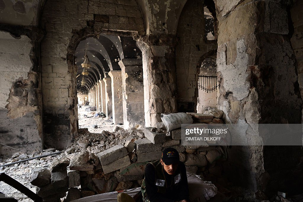 A Syrian rebel fighter takes a rest at a destroyed section of the Umayyad Mosque complex in the old city of Aleppo on April 16 2013 After nine months...